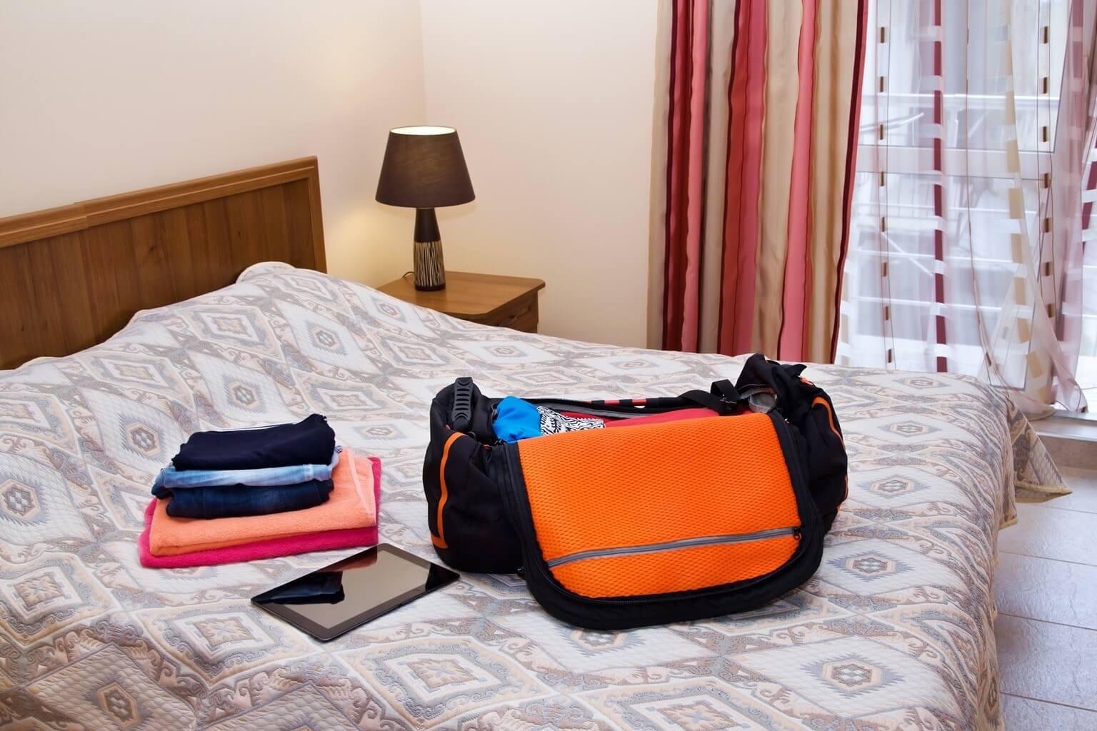 Logement en Irlande : Chambre d'hôtel avec bagage ouvert, linge et tablette